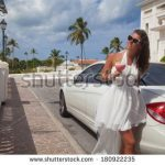 stock-photo-happy-woman-in-the-luxury-white-car-with-cocktail-at-valentine-s-day-beautiful-rich-brunette-woman-180922235
